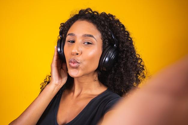 Afrikaanse jonge vrouw die hoofdtelefoons draagt die een selfie op gele achtergrond maken.