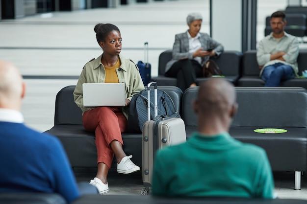 Afrikaanse jonge vrouw zitten en met behulp van haar laptop tijdens de vergadering in de wachtkamer van de luchthaven