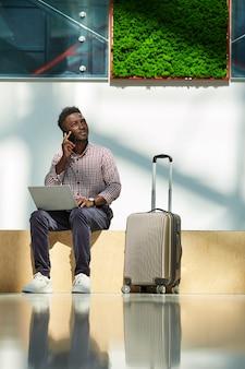 Afrikaanse jonge zakenman die op mobiele telefoon spreekt en laptop uisng terwijl hij op de luchthaven zit die hij vliegtickets bestelt
