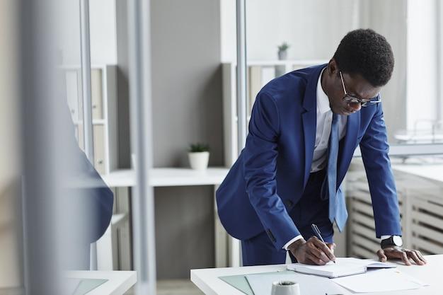 Afrikaanse jonge zakenman planning van zijn bedrijf in notitieblok aan de tafel op kantoor