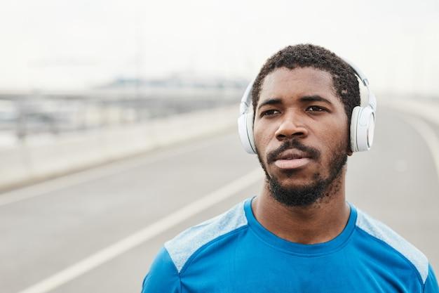 Afrikaanse jongeman die een draadloze koptelefoon opzet en naar muziek luistert tijdens het hardlopen in de buitenlucht