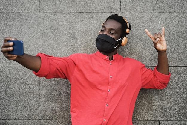 Afrikaanse jongeman luisteren muziek op mobiele telefoon app terwijl het dragen van beschermend masker - focus op gezicht