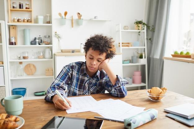 Afrikaanse jongen die in zijn notitieboekje schrijft dat hij zijn huiswerk doet terwijl hij thuis aan de tafel in de keuken zit