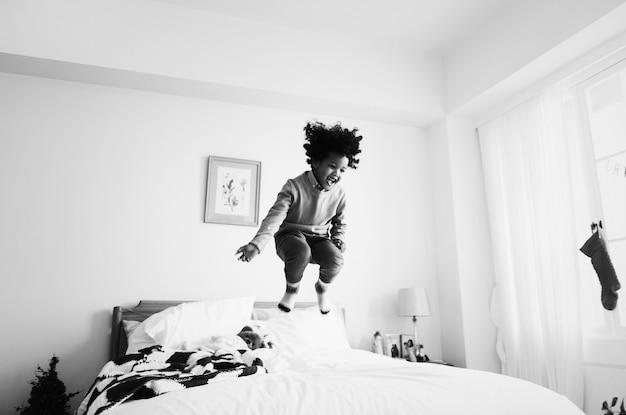 Afrikaanse jongen die plezier heeft met springen op het bed