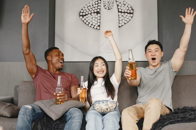 Afrikaanse jongen en aziatisch paar kijken naar voetbal, eten popcorn en drinken bier. vrienden die voor een voetbalteam wroeten. mensen zijn blij.