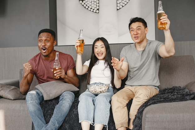 Afrikaanse jongen en aziatisch paar kijken naar voetbal, eten popcorn en drinken bier. vrienden die voor een voetbalteam wroeten.