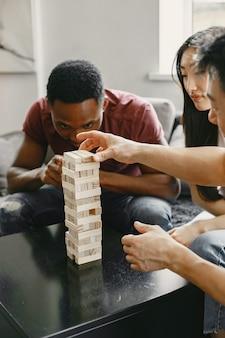 Afrikaanse jongen en aziatisch stel die jenga spelen speel bordspel in vrije tijd