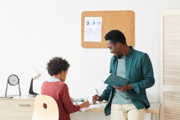 Afrikaanse jongen zit aan bureau en studeert met zijn leraar thuis leraar uitleggen van het nieuwe materiaal