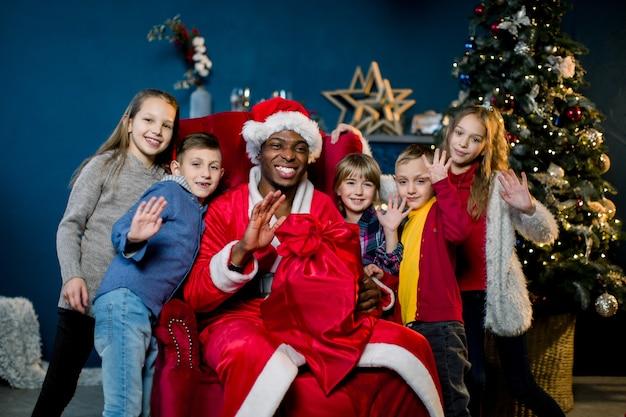 Afrikaanse kerstman en gelukkige kleine kinderen op de achtergrond van de kerstboom