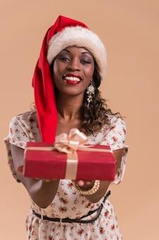 Afrikaanse kerstmisvrouw die de gift van de de hoedenholding van de kerstman draagt