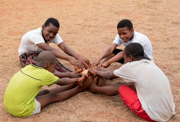 Afrikaanse kinderen met voetbal bal zitten
