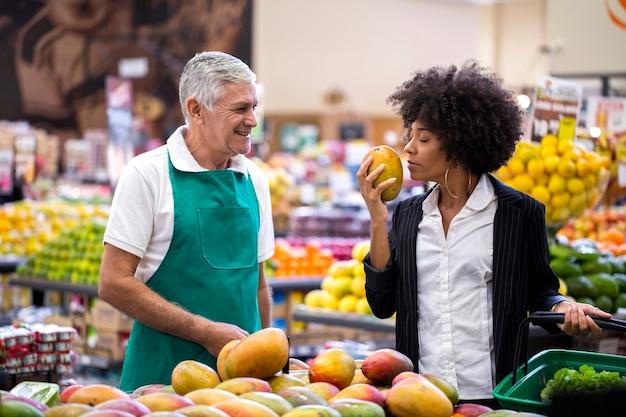 Afrikaanse klant met groenteman, die mango houdt.
