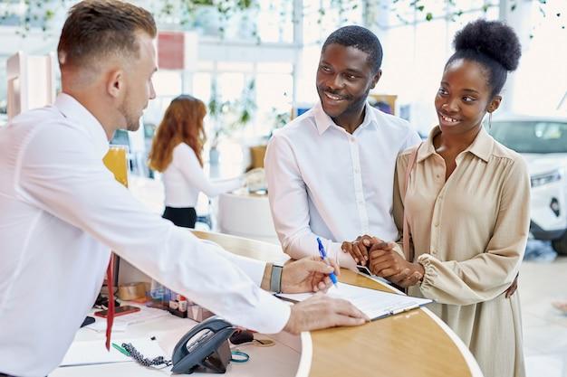 Afrikaanse klanten ondertekenen papieren met verkoper in dealer winkel
