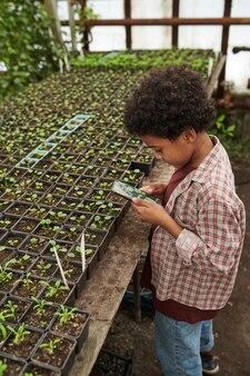 Afrikaanse kleine jongen die mobiele telefoon gebruikt en een foto maakt van zaailingen in de kas