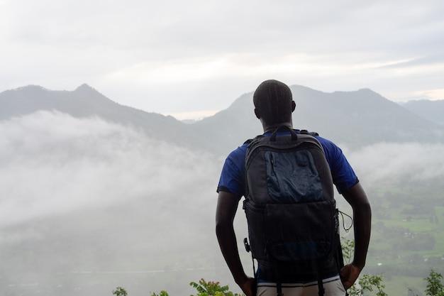 Afrikaanse klimmers die op de bovenkant van de heuvel kijken die met mist wordt behandeld.