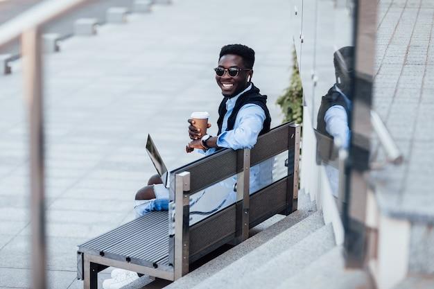 Afrikaanse knappe jonge zakenman die op een bankje zit met zijn laptop op een zonnige straat naast een park. met kopje koffie. levensstijl.