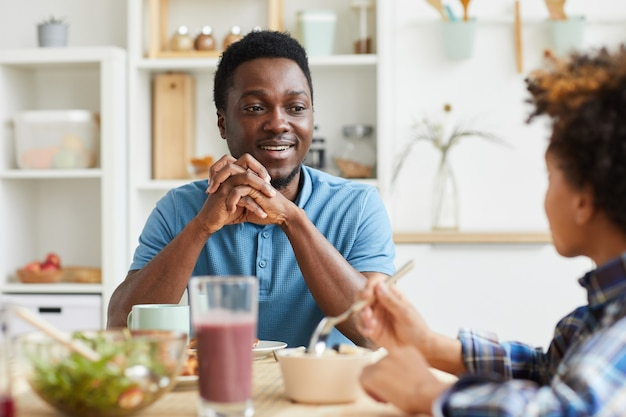 Afrikaanse lachende vader in gesprek met zijn zoon zittend aan tafel tijdens het ontbijt thuis