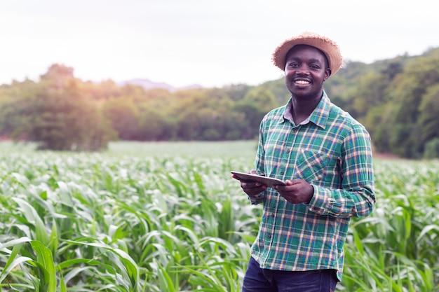 Afrikaanse landbouwerstribune in het groene landbouwbedrijf met holdingstablet