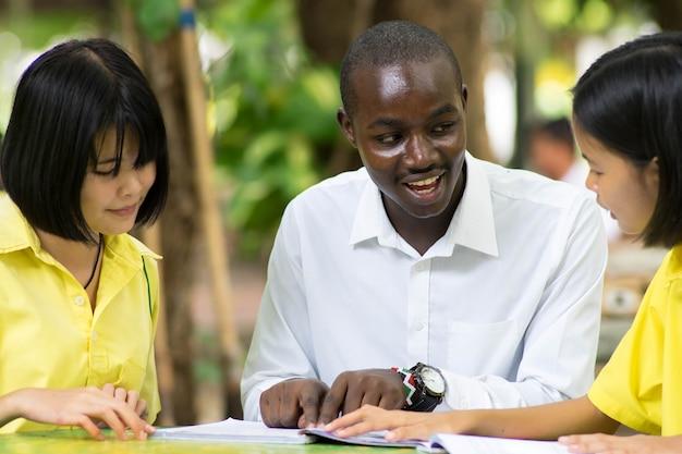 Afrikaanse leraar die aziatische student over vreemde talen onderwijst.