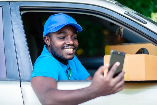 Afrikaanse leveringsmens die slimme telefoon in de auto kijken