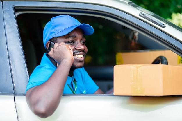 Afrikaanse leveringsmens die telefonisch in de auto spreekt