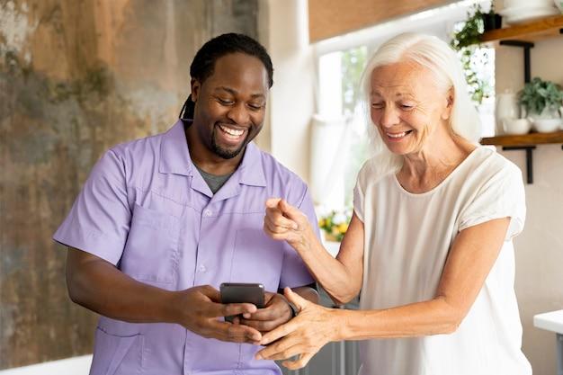 Afrikaanse maatschappelijk werker die een oudere vrouw helpt