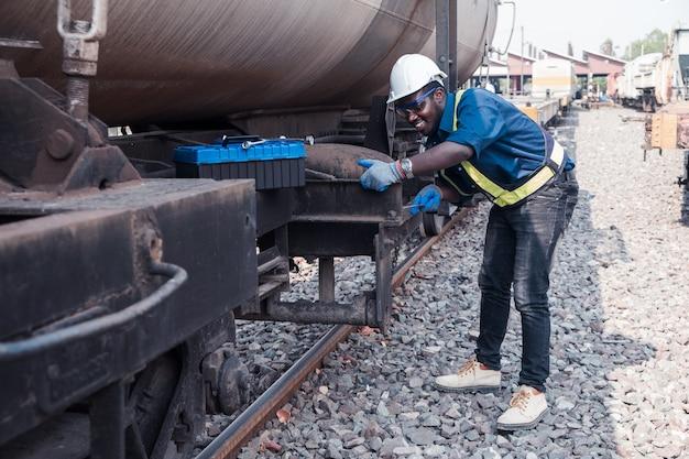 Afrikaanse machine-ingenieur die een helm, bosjes en veiligheidsvest draagt, gebruikt een moersleutel om het gas en de olie van het treintransport te repareren