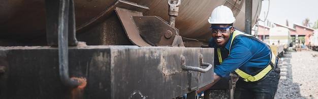 Afrikaanse machinetechnicus die een helm, bosjes en veiligheidsvest draagt, gebruikt een moersleutel om de trein te repareren