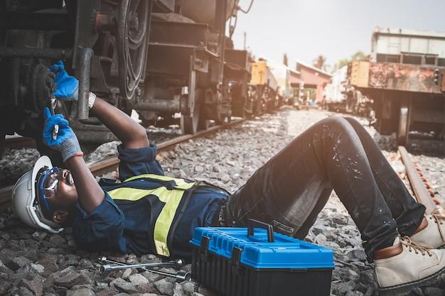 Afrikaanse machinetechnicus die liegt en een helm, bosjes en veiligheidsvest draagt, gebruikt een moersleutel om de trein te repareren