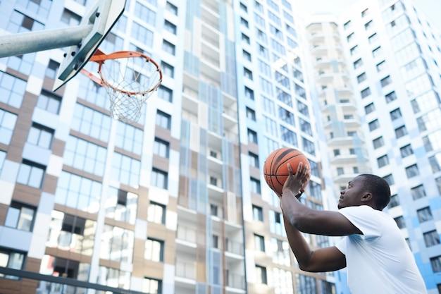 Afrikaanse man bal gooien naar hoepel