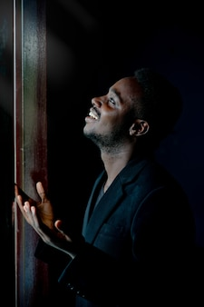 Afrikaanse man bidden voor god in een donkere kamer.
