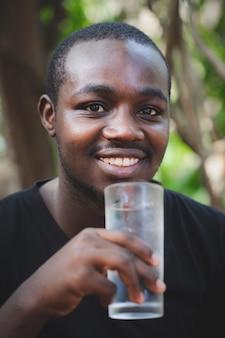 Afrikaanse man die een glas water vasthoudt, drinkt schone, heldere minerale aqua voor lichaamsverfrissing. hydratatie concept