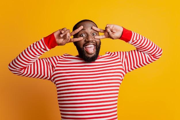 Afrikaanse man die vredesteken maakt bedek oog gek gezicht open mond op gele achtergrond