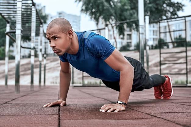 Afrikaanse man doet plank in openluchtgymnastiek in de buurt van het park