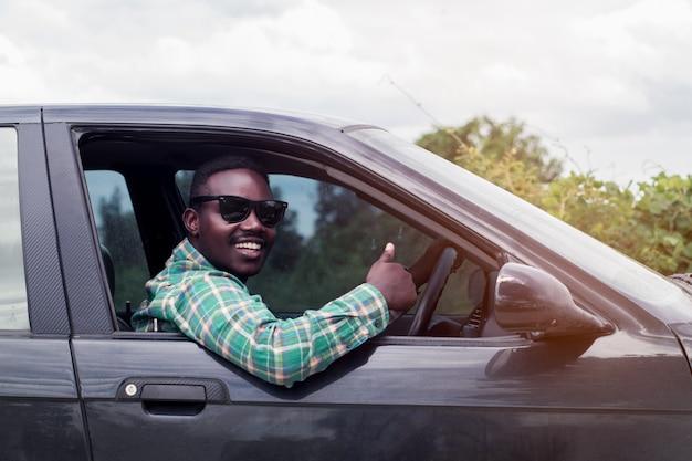 Afrikaanse man draagt â € <â € <een zonnebril en lacht tijdens de vergadering in een auto met open voorruit.