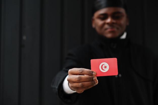 Afrikaanse man draagt zwarte durag houdt tunesische vlag bij de hand geïsoleerde donkere muur.