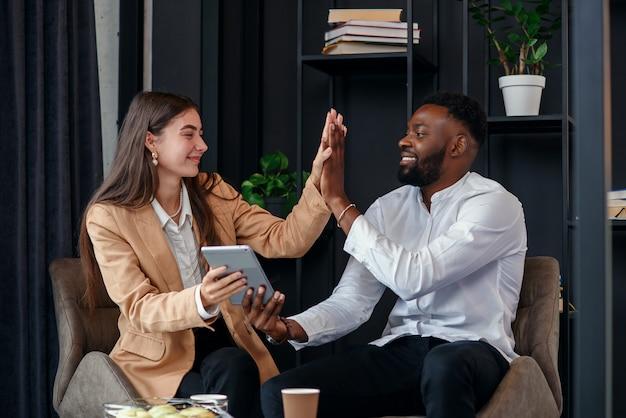 Afrikaanse man en blanke vrouw hebben koffiepauze op kantoor toilet aan tafel in de buurt van raam drinken warme espresso.