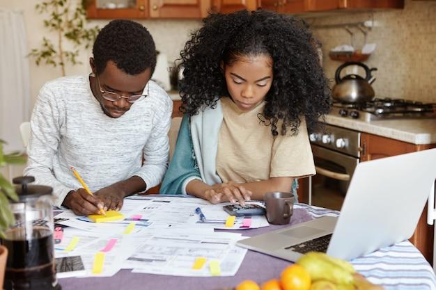 Afrikaanse man en vrouw zitten aan de keukentafel met papieren en laptop pc, binnenlandse financiën samen beheren: vrouw rekenen op rekenmachine terwijl man notities maken met potlood. gezinsbudget