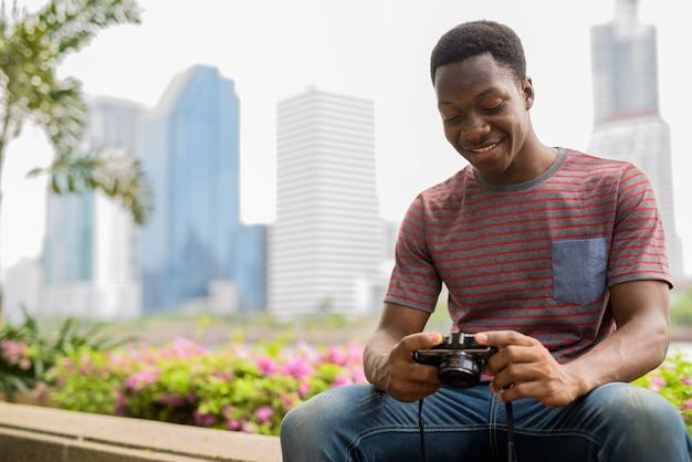 Afrikaanse man fotograaf op zoek naar foto's van de camera in het park