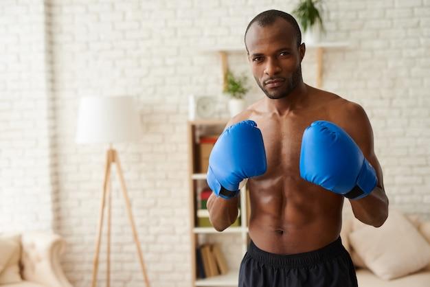 Afrikaanse man in bokshandschoenen staat in het bestrijden van houding