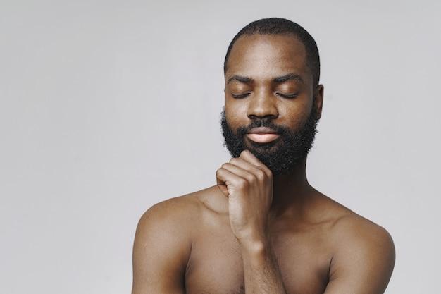 Afrikaanse man in een studio. witte muur. man zonder kleren.