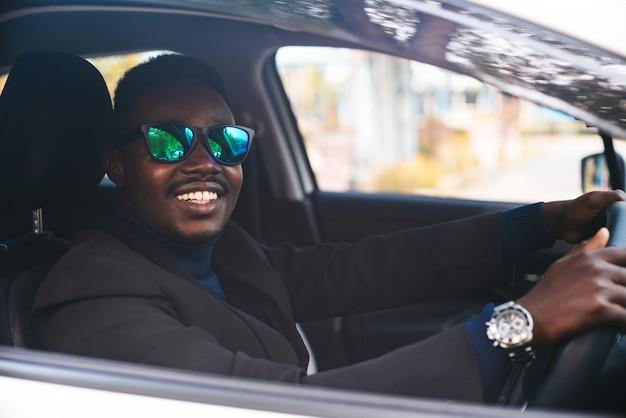 Afrikaanse man in een zwart pak zit achter het stuur met een glimlach en gelukkig
