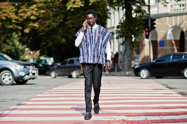 Afrikaanse man in traditionele kleding en glazen lopen op zebrapad en spreken op mobiele telefoon