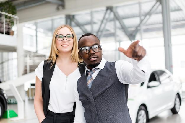 Afrikaanse man in zonnebril toont het meisje aan de zijkant av de showroom