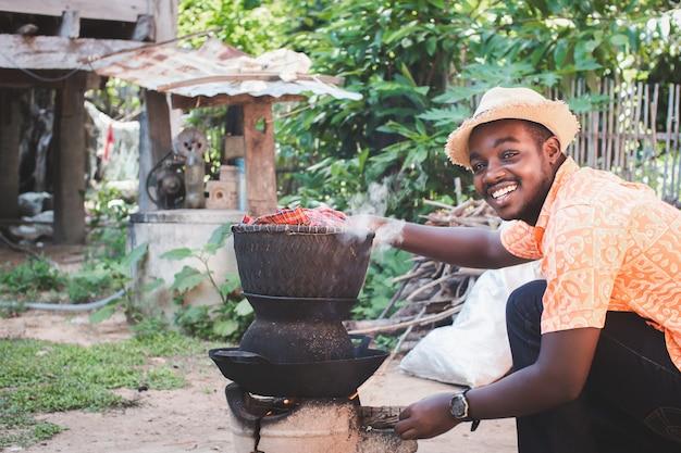 Afrikaanse man kookt graag met een houtskoolfornuis