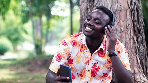 Afrikaanse man luisteren naar muziek van smartphone met draadloze koptelefoon met glimlach en gelukkig