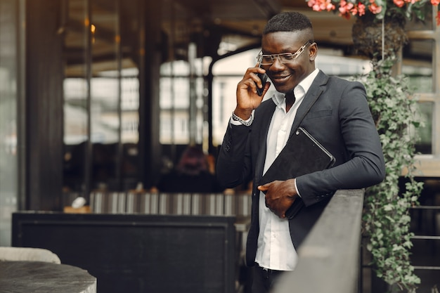 Afrikaanse man. man in een zwart pak. mannetje met een mobiele telefoon. zakenman op kantoor.