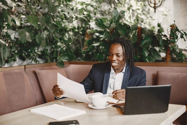 Afrikaanse man. man in een zwart pak. mannetje met een notitieboekje.