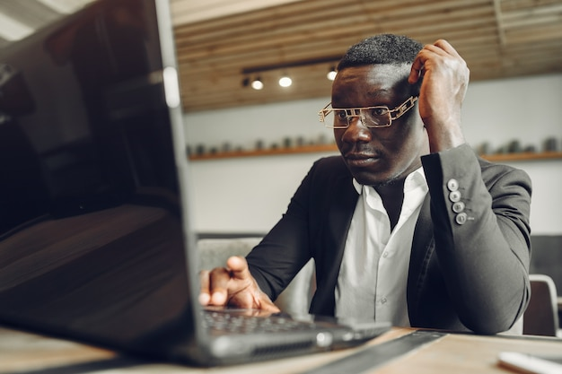 Afrikaanse man. man in een zwart pak. mannetje met laptop. zakenman op kantoor.