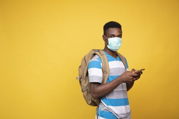 Afrikaanse man met een rugzak die een gezichtsmasker draagt en zijn telefoon gebruikt tegen een gele achtergrond
